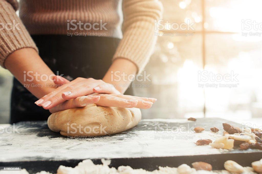 Female hands kneading dough, sunset background stock photo