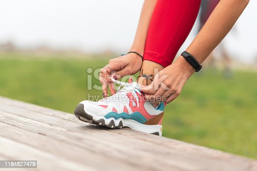 istock Female hands lacing running shoes 1184827479