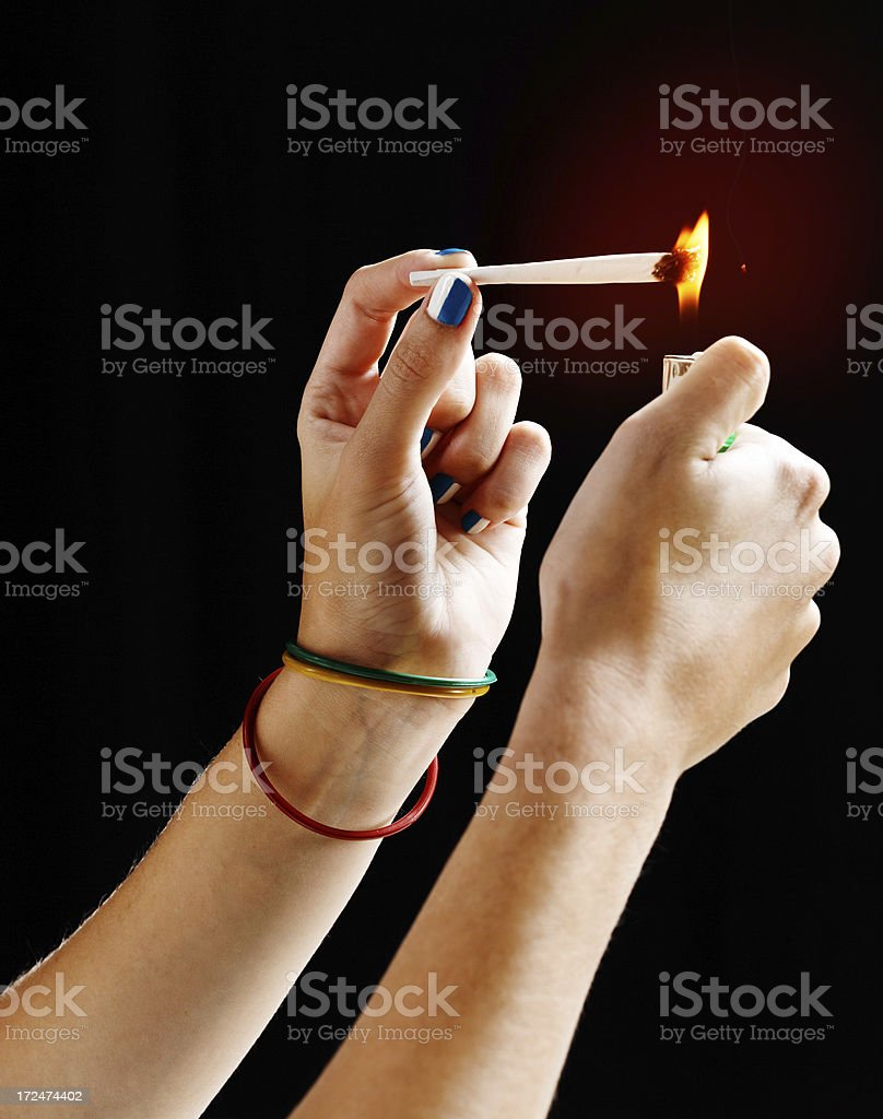 Female hands lighting hand-rolled joint of marijuana royalty-free stock photo