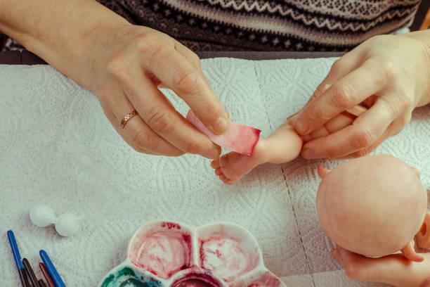 weibliche hände machen puppen bjd oder wiedergeboren am arbeitsplatz. bearbeitung des werkstücks. das konzept des handwerks der meister hersteller von puppen. selektiven fokus. - wiedergeborene babys stock-fotos und bilder