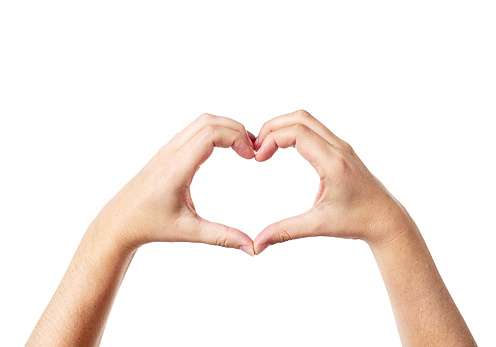 A woman's hands make a heart shape against a white background.