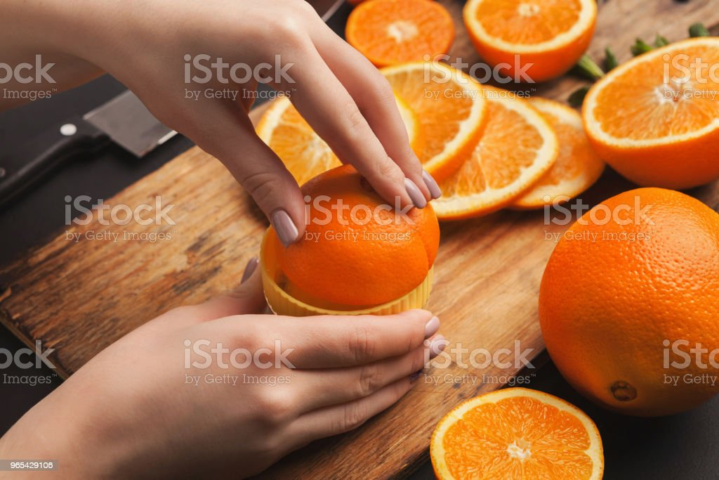 Female hands making orange juice, closeup royalty-free stock photo