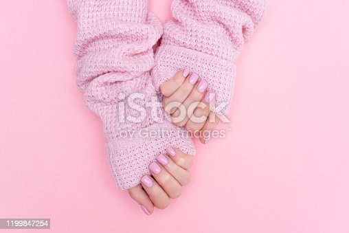 946930880 istock photo Female hands manicure close up view on pink knitted sweater background. Nail painting effects. Manicure salon banner concept 1199847254