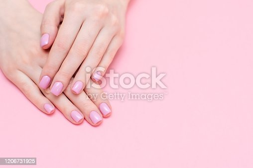 946930880 istock photo Female hands manicure close up view on pink knitted sweater background. Nail painting effects. Manicure salon banner concept 1206731925