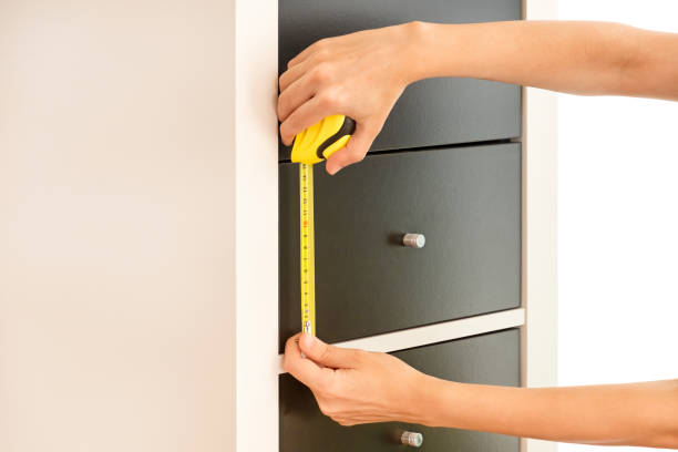 Female Hands Measuring The Height Of Drawers With An Automatic Tape Measure stock photo