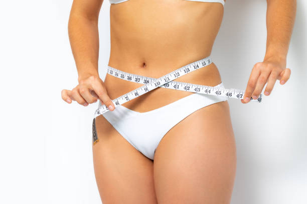 Female hands measuring waist with measure band. stock photo