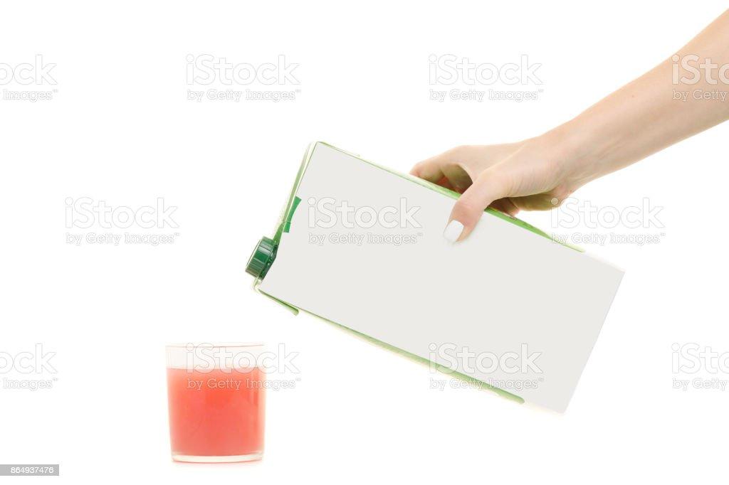 Fêmea mãos multi-camadas suco em uma caixa de papelão e em um copo - foto de acervo