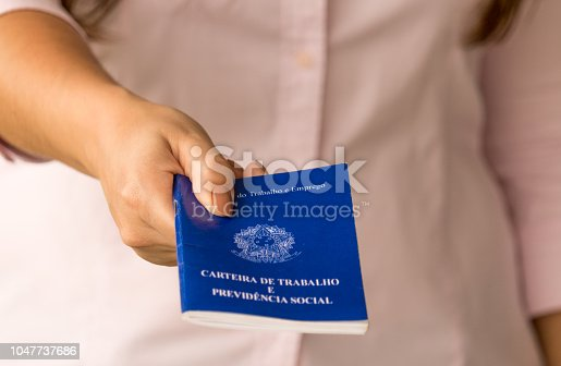 istock Female hands of a worker holding a portfolio work permit of the Ministry of Labor and Social Security of Brazil. 1047737686
