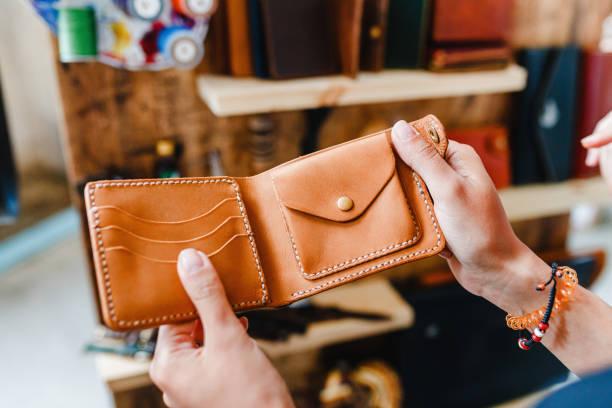 weibliche hände des kunden, der handgefertigte ledertasche auf dem hintergrund eines ladens ausprobiert - leder portemonnaie herren stock-fotos und bilder
