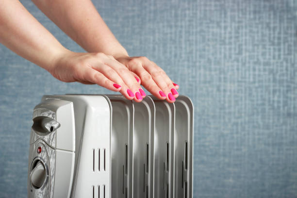 Female hands on electric oil radiator close-up on blue background stock photo