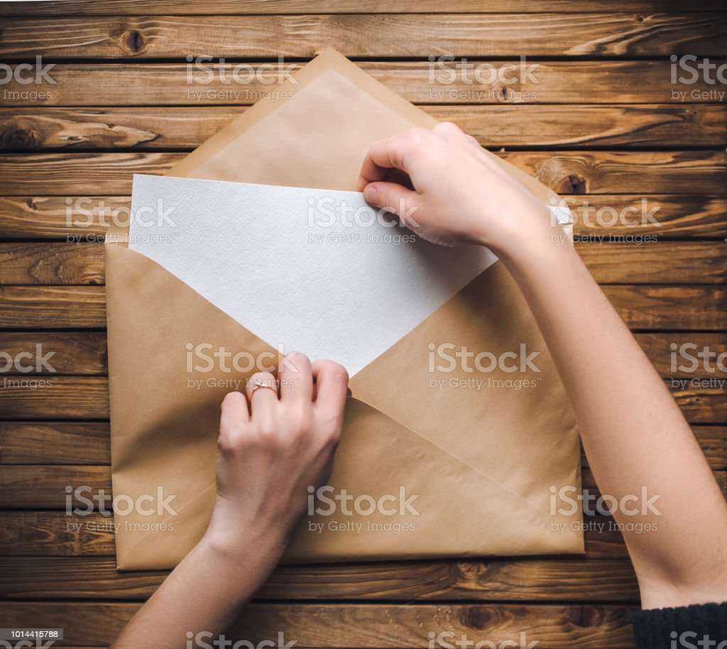 Female hands open a large brown envelope and take out a letter from...