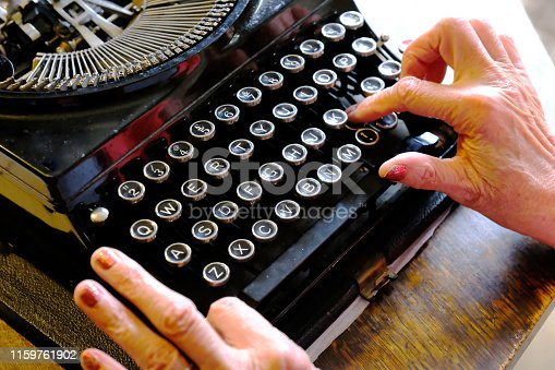 Close-up of a pair of female hands operating an old-fashioned typewriter which is sitting on a wooden desk.