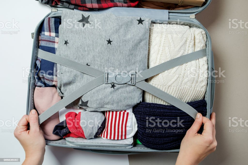Female hands packed clothes in suitcase. Winter vacations and...