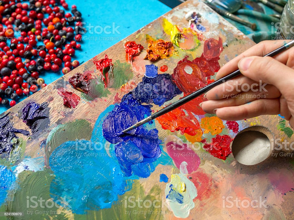 Female hands, paint brushes, oil paints and palette stock photo