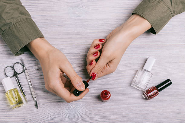 female hands painted nails with red lacquer - nägel lackieren stock-fotos und bilder