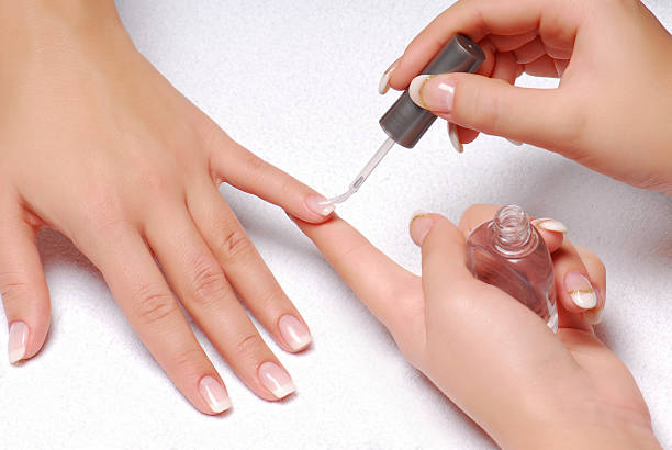 Female Hands Painting A Womans Nails With Clear Varnish Stock Photo