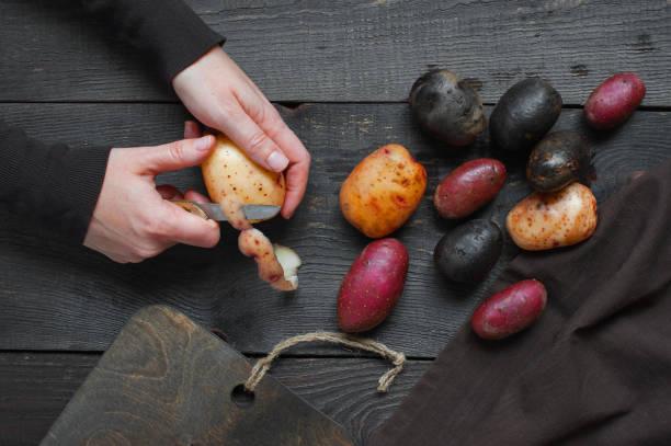 weibliche hände schälen frische kartoffeln - küche lila stock-fotos und bilder