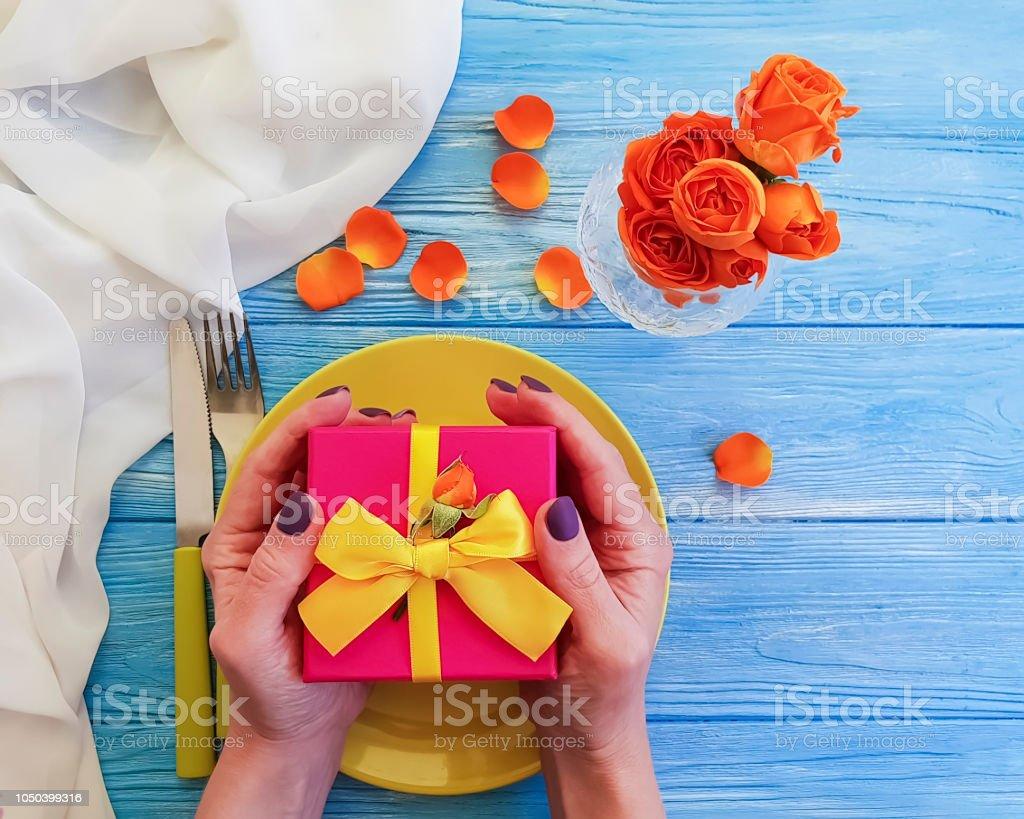 female hands plate, fork, knife gift box flower rose on wooden