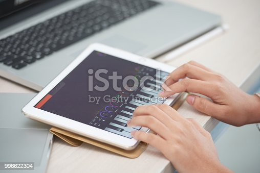 istock Female hands playing piano app on tablet 996622304