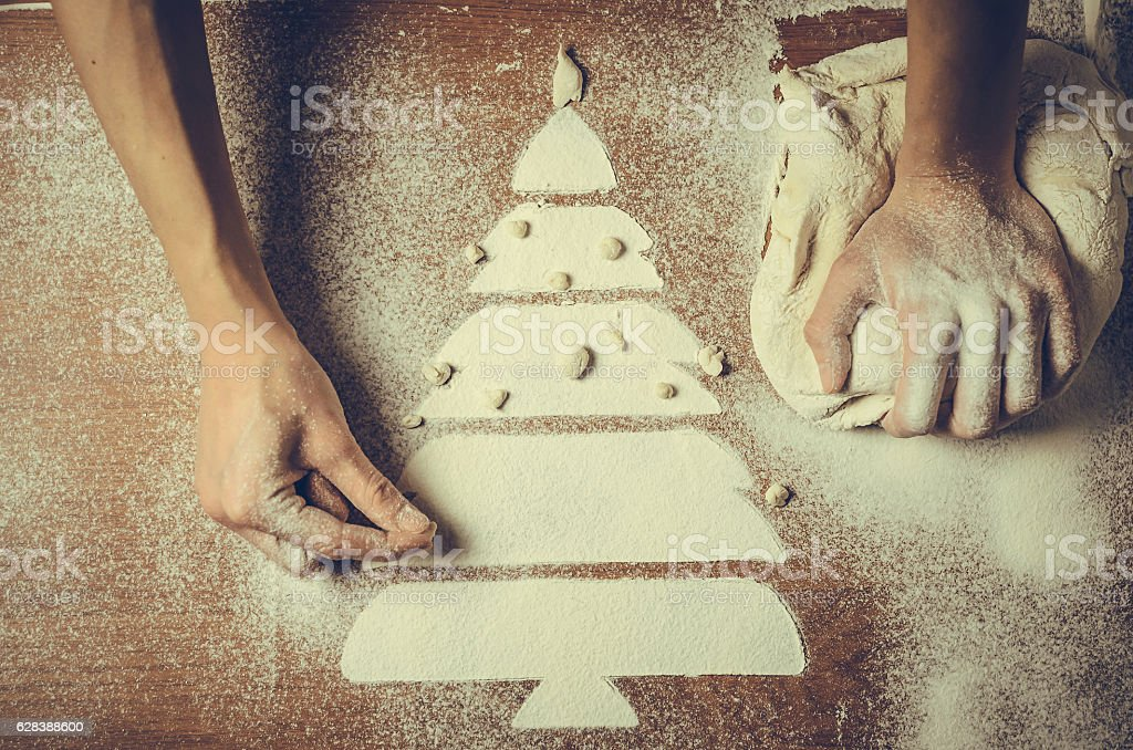 Female hands pressing dough and make the Christmas cookies foto royalty-free