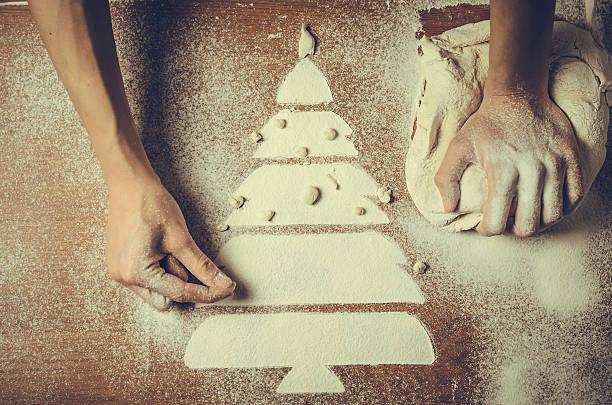 Female hands pressing dough and make the Christmas cookies - foto de acervo
