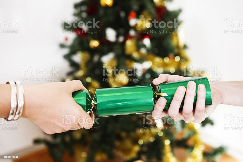 Female hands pull shiny green Christmas cracker stock photo
