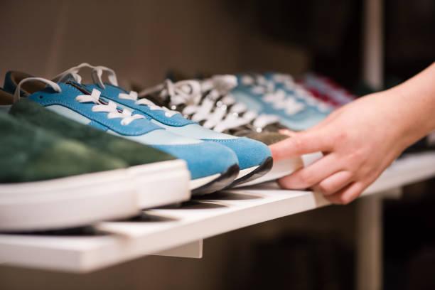 vrouwelijke hands put sneakers collectie op de winkel rack - shoe stockfoto's en -beelden