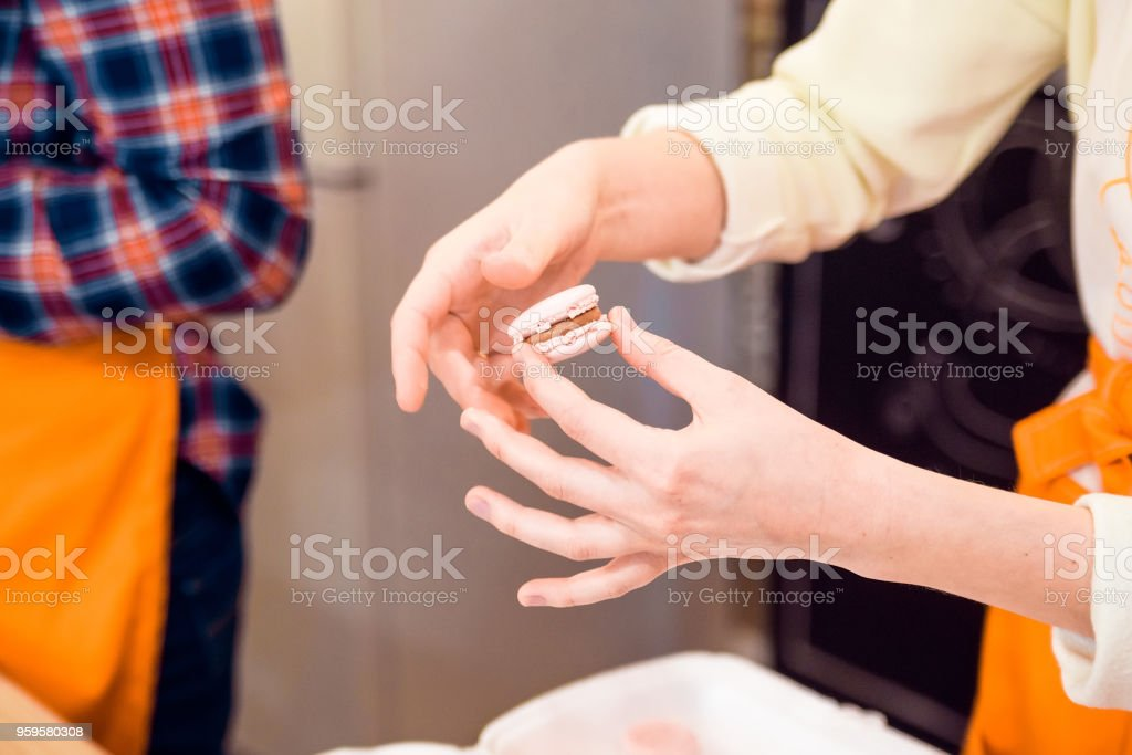 Female hands put together French macaron stock photo