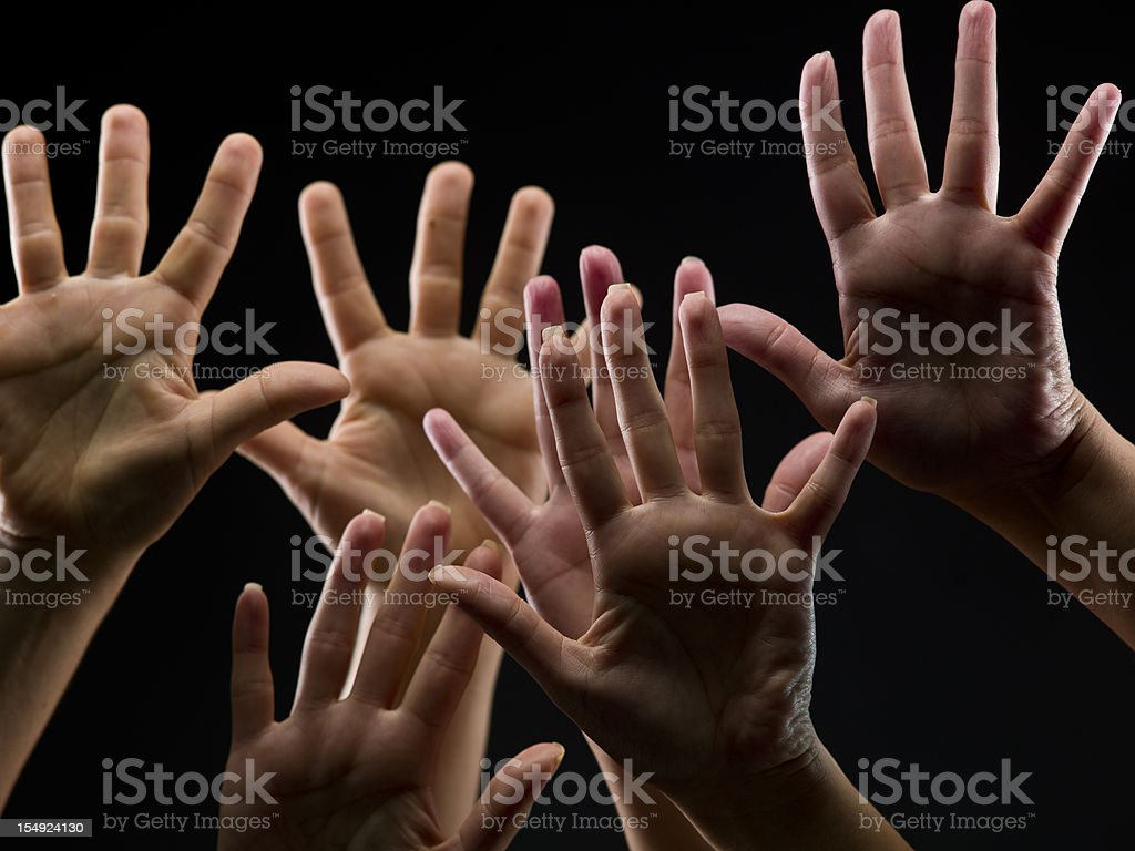 Female hands reaching into the air on a black background. royalty-free stock photo