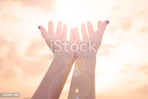 974882202istockphoto Female hands Reaching the sun with lens flare 540981488