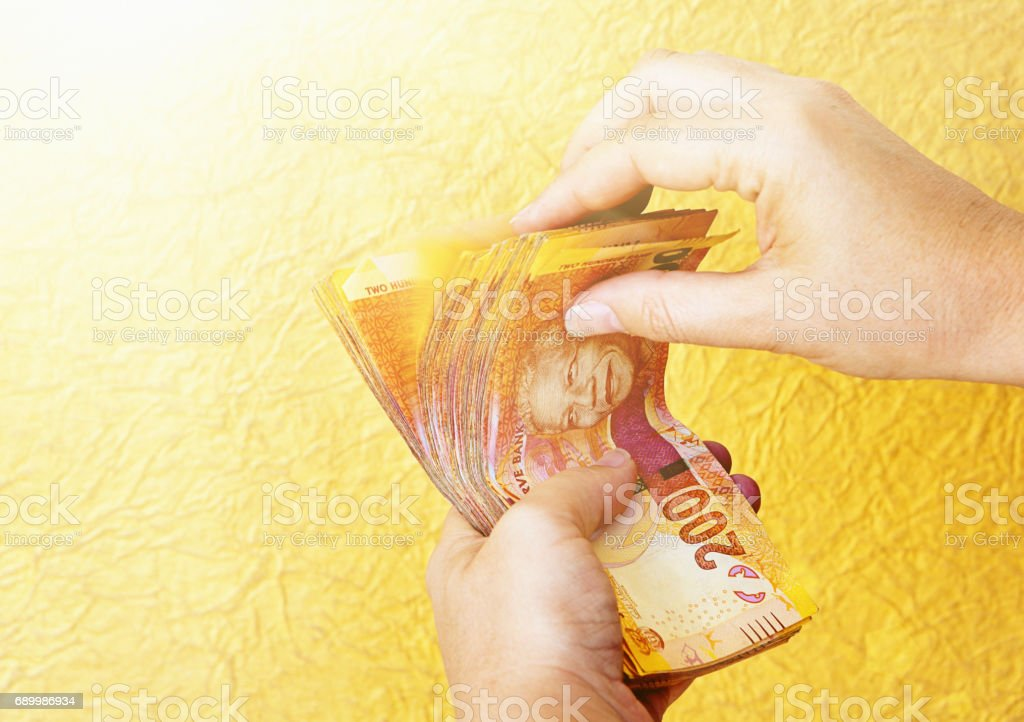 Female hands riffle through South African R200 banknotes, counting stock photo