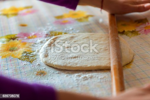 673400318istockphoto female hands rolling raw dough on white table 639708076