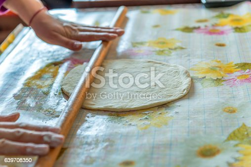 673400318istockphoto female hands rolling raw dough on white table 639708350