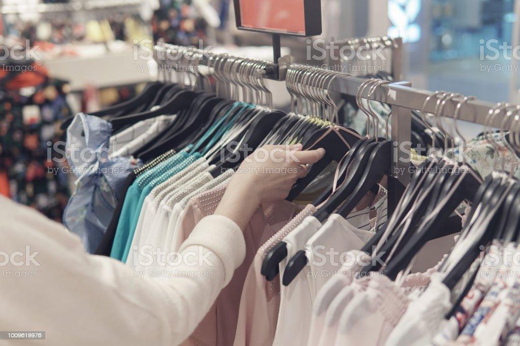 Weibliche Hände stöbern in Kleidung in einem Second-Hand-shop – Foto