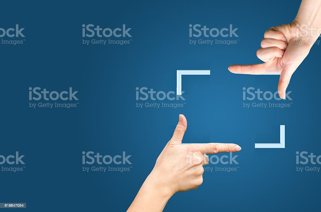 Female hands showing cropping composition gesture. Isolated on blue. stock photo