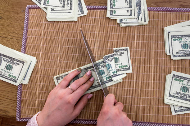 Female hands slicing dollar banknotes on bamboo mat Female hands slicing dollar banknotes on bamboo mat devaluation stock pictures, royalty-free photos & images