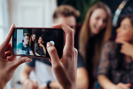 Female hands taking photo with smartphone of young cheerful friends, blurred background