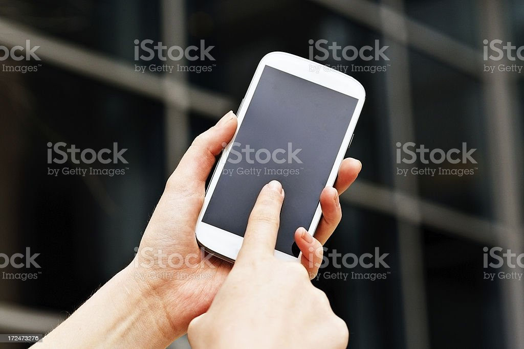 Female hands tap smart phone touch screen outside building royalty-free stock photo