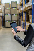 Vertical color image of businesswoman - unrecognizable person - touching a digital tablet screen in large futuristic storage compartment. Woman standing in aisle of distribution warehouse with touchscreen tablet in hand. Focus on businesswoman's hand holding black tablet, futuristic warehouse full of packages for sending in background. Logistics, freight, shipping, receiving.