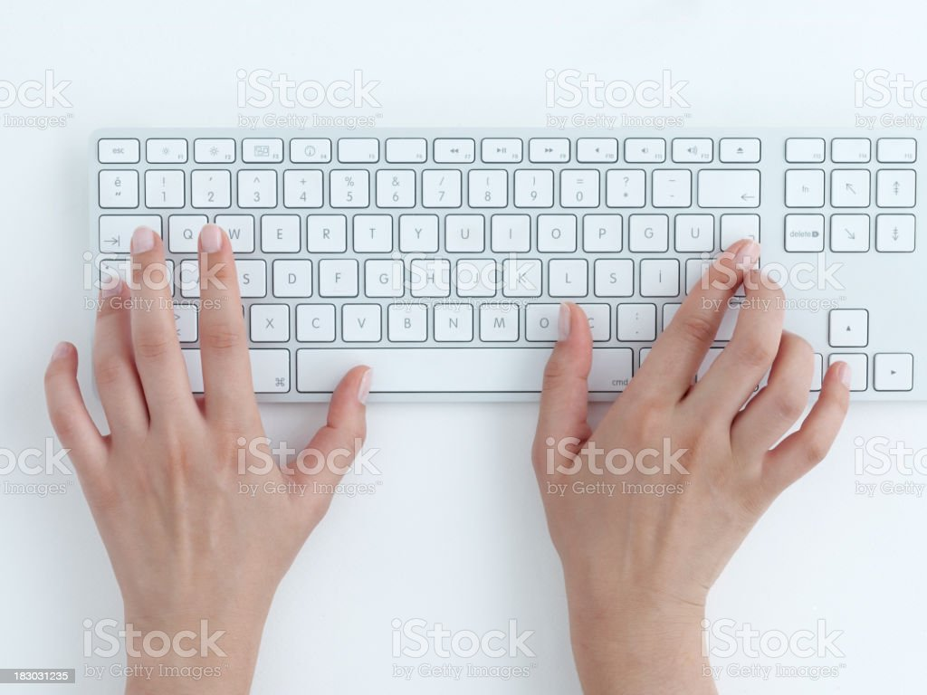 Female hands typing on a white computer keyboard stock photo