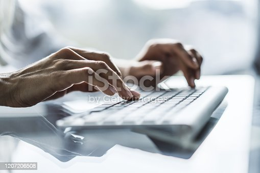 Female hands typing on computer keyboard in sunny office, business and technology concept. Close up