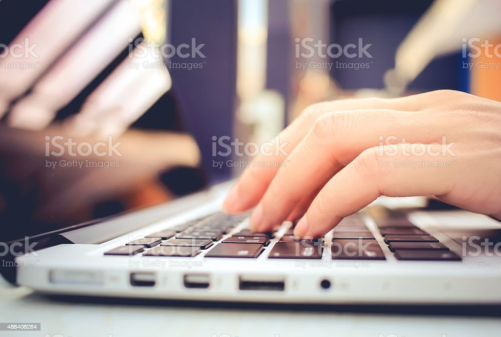 Female hands typing on keyboard of laptop stock photo