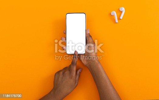 Listen music online. Black female hands using smartphone with blank screen and wireless earphones on orange background,