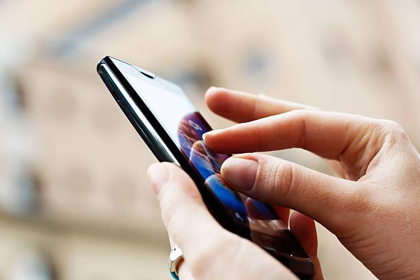 Female hands using Sony Ericsson Xperia X10 smart phone stock photo