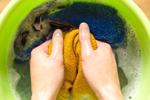 weibliche hände waschen farbe kleidung im becken - fleckenentferner stock-fotos und bilder