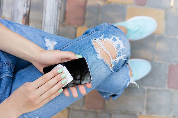 weibliche hände tuch die touchscreen-telefon antibakterielle tücher - unhygienisch stock-fotos und bilder