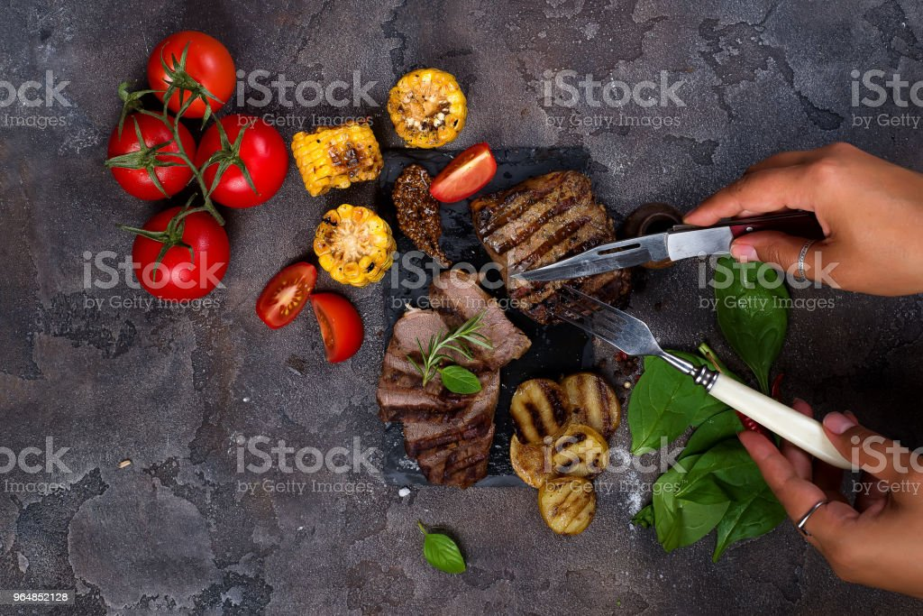 Female hands with a fork and knife cut Beef steak and grilled vegetables on slate board on stone table. royalty-free stock photo