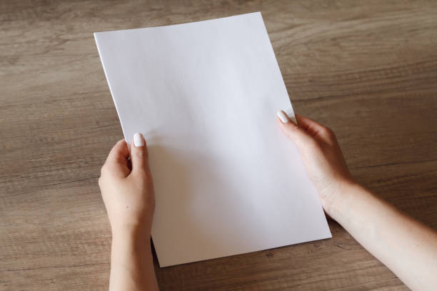 female hands with a sheet of paper stock photo