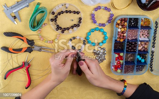 1074436306istockphoto Female hands with a tool on a yellow background. Making bracelet of colorful beads 1007239924