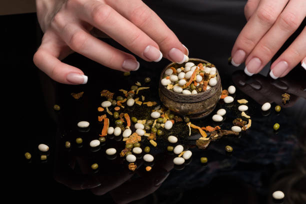 Cтоковое фото Female hands with beautiful French manicure gather the haricot scattered on a black background, peas, dried vegetables and spices in a vintage melkhiorovy saltcellar